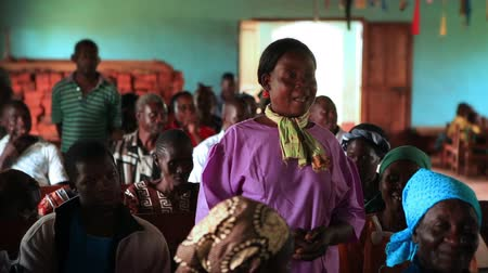 igreja : A woman standing in the middle of a church congregation speaks while those around her listen. Filmed in Kenya, Africa. Vídeos