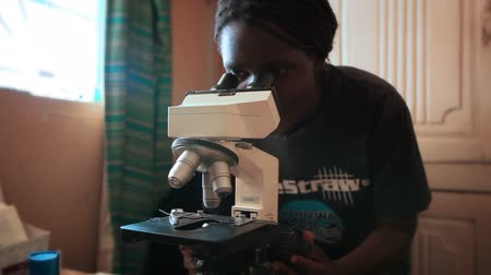 przychodnia : An African woman in a t-shirt bends over to study something through a microscope. Filmed in Kenya, Africa.