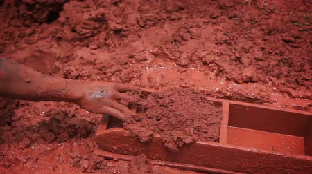 blocos : Close up of clay being expertly shaped into brick molds and carried to drying spot. Filmed in Kenya, Africa. Vídeos