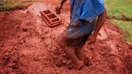 kalhoty : Close up of mans feet stepping on red clay to mix it for brickmaking. Footage zooms out to show the man and his surroundings. Filme din Kenya, Africa.