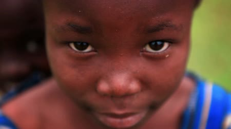 black dirt : Racking extreme close up of a young black girl looking at the camera. Another child peeks over her shoulder. FIlmed in Kenya, Africa.