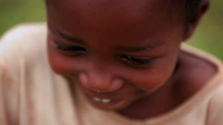 vigyorgó : Racking extreme close up of a young black boy laughing shyly and looking away from the camera. Filmed in Kenya, Africa.