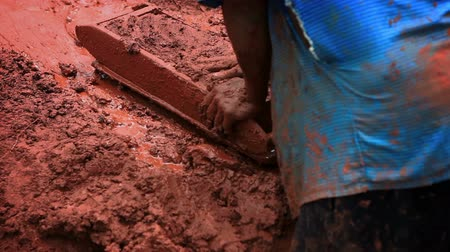 kalhoty : Close up footage behind a man molding brick; another man replaces him to shovel clay into the brickmolding area. FIlmed in Kenya, Africa.