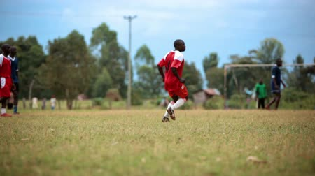 kalhoty : Footage following the action of a Kenyan footballsoccer game between two teams of young men, a red team and a blue team. Filmed in Kenya, Africa.