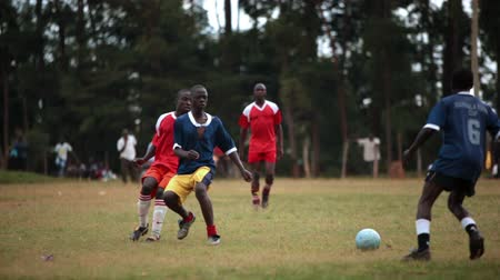 kalhoty : Wild footage following the action of a Kenyan footballsoccer game between two teams of young men, a red team and a blue team. Filmed in Kenya, Africa.