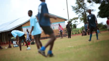 kalhoty : Footage following the action of a Kenyan footballsoccer game between two teams of young men, a light blue team and a blue team. Filmed in Kenya, Africa.