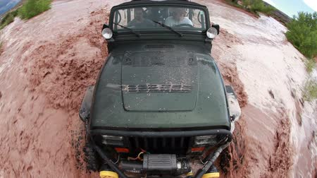 vysoký úhel pohledu : High angle probe view of a jeep driving through the muddy waters of the Colorado River, Moab Utah.
