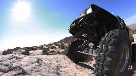 diretamente : Traveling probe view of a jeep climbing a big rock formation, getting stuck with the wheel directly in front of the camera, camera moves to see the front side of jeep on rock, filmed on a beautiful sunny day, located in Moab Utah.