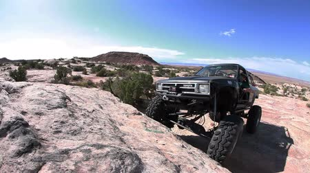 diretamente : Side angle stationary probe view of a jeep climbing a big rock formation, getting stuck with the wheel directly in front of the camera, and reversing down the rock, filmed on a beautiful sunny day, located in Moab Utah.