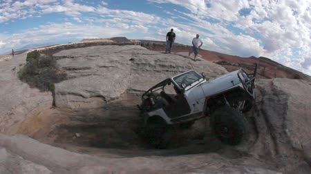droga : Stationary probe view of a white jeep slowly climbing a steep rock with two men in the distance watching, located in Moab Utah. Wideo