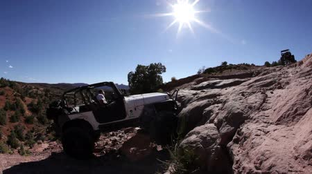 rocks red : White Jeep crawling up and over a large rock in Moab, Utah. Smoke pumps out from under the tires as the driver careens upwards over the ledge.