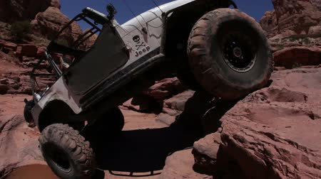 terreno extremo : A white jeep climbs up a rock in Moab desert, Utah. Filmed on a clear day.