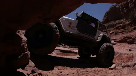крайняя местности : A white jeep is trying to climb up a cliff but gets stuck in the end. The back wheels are spinning. Filmed from the side from a cave nearby in Moab desert, Utah. Captured on a clear day.