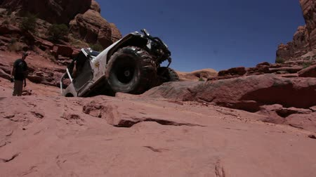nem sikerül : A white jeeps tries to climb on a cliff but fails and starts swaying while one person watches it on the side. Filmed from front in Moab desert, Utah on a clear day. Stock mozgókép