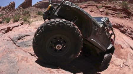 wspinaczka : A murky jeep is trying to climb up a cliff in Moab desert but fails. Filmed on a clear day.