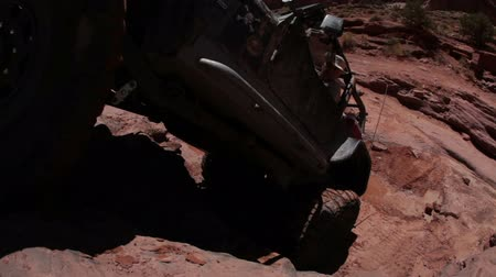 крайняя местности : People watch while a jeep tries to climb up a cliff. It manages to get halfway up but then stops and starts falling back. Filmed on Moab desert on a clear day.