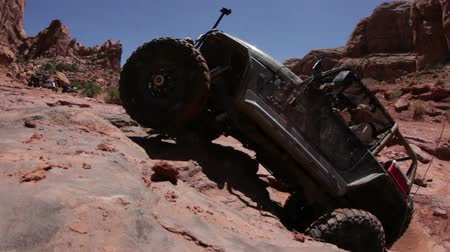 nem sikerül : A black jeep fails when trying to climb up a cliff and falls back. Some people are watching. Filmed in Moab desert on a clear day. Stock mozgókép