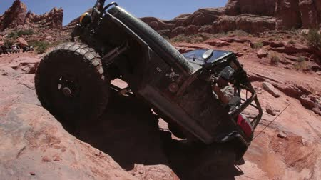 kerék : A black jeep attempts to get up a cliff but keeps failing and falling back. Some people are standing behind and watching. Filmed in Moab desert on a clear day.