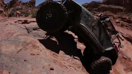 крайняя местности : A driver is trying to lead his jeep up a cliff but fails and backpedals. Some people are watching. Filmed on a clear day in Moab desert. Стоковые видеозаписи