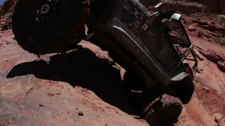nem sikerül : A driver is trying to lead his jeep up a cliff but fails at it and backs off. Some people are watching. Filmed on a clear day in Moab desert.
