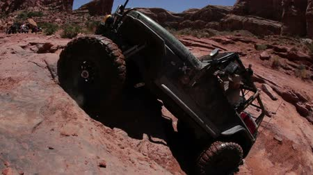 крайняя местности : A black jeep is attempting to climb up a cliff but fails and backs off. People are standing behind it and watching. Filmed on a clear day in Moab desert.