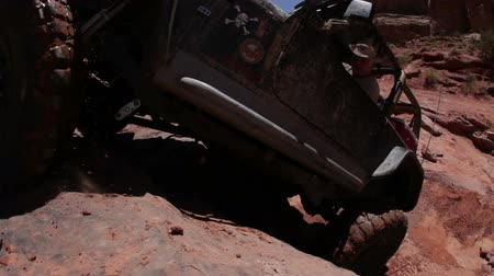 autó : A jeep attempts to climb up a cliff in Moab desert but fails and falls close to the camera. The cameraman backs away hurriedly as the Jeep comes close. Filmed on a clear day.
