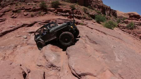 upadek : A jeep fails at climbing up a cliff and starts to fall over when the scene cuts. Filmed on a clear day in Moab desert, Utah. Wideo