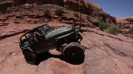 крайняя местности : A jeep successfully climbs up a cliff in Moab desert, Utah. Filmed on a clear day.