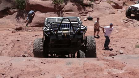 kerék : A white jeep climbs up a cliff in Moab desert while people stand behind it and watch. Filmed from front on a clear day. Stock mozgókép
