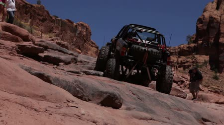 fennsík : Stationary shot of black jeep slowly climbing a steep slope in Moab, UT. Video closes with the jeep getting stuck. Several men look on.
