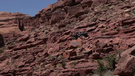 rocks red : Black Jeep climbing over the red rocks in Moab, Utah.