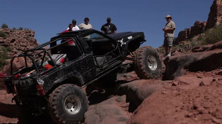pincel : Black truck tries is scale rocks in Moab, but slides back down. Several men stand at the top o the rocks and look on. Vídeos