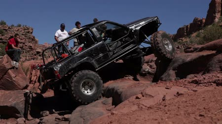 fenda : Stationary shot of black Jeep spinning its tires as it is stuck on a steep, bumpy slope in Moab, UT. Several men look on.