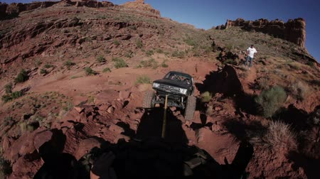 fennsík : Shot from the back of a Jeep pulling a truck up a steep dirt path in Moab, Utah Stock mozgókép