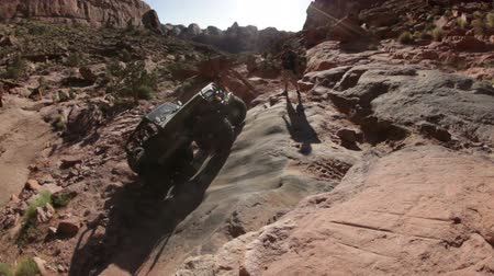 fenda : Stationary shot of man watching a Jeep struggle to climb a steep desert slope in Moab, UT