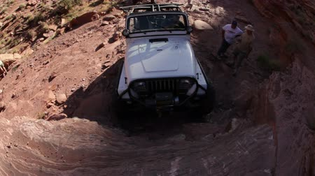 dik : Jeep attempts to climb an extremely steep rock face that it is almost perpendicular to the ground beneath it. Stok Video