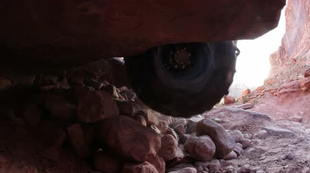 fenda : Shot from a crevice under the rock a Jeep drives up.
