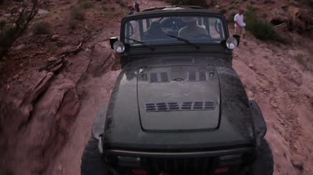скат : View of the front of a Jeep as is climbs up rocks in Moab, Utah. Men stand beside it and another Jeep can be seen on a lower level of rock.