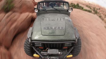 pedregulho : Sped up shot of a black Jeep driving the rocky terrain in Moab. The fish-eye lens creates an element of steep drop offs on the side of the rocks. The rock give way into a muddy dirt path. Stock Footage