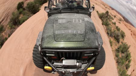 fennsík : Front view of a black Jeep navigating precarious red rock in Moab, Utah. The fish-eye distortion creates a steep drop off on the sides of the shot.