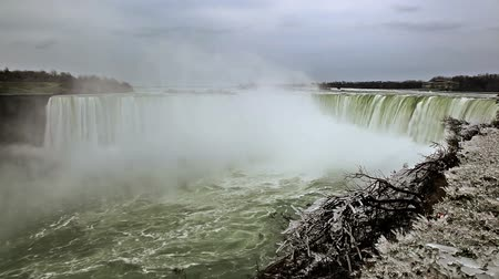 narożnik : Stationary shot of Horseshoe falls on a cloudy winter day. There is snow-covered foliage in the bottom right corner. The shore can be seen in the distance.