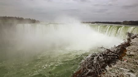 Онтарио : Stationary front view of Horseshoe falls. The sky is completely covered with clouds. Snow lightly dusts the nearby foliage.