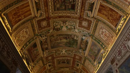 freska : Low-angle tracking footage of the ornate frescoes and crown molding gracing the ceiling of the Gallery of Maps within the Vatican Museums.