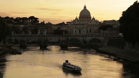 watykan : St Peters Basilica and the Ponte SantAngelo make the background of a boat travelling down the Tiber River during an orange sunset. Wideo