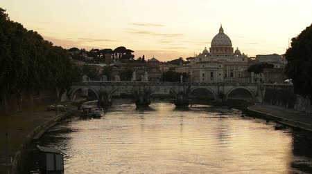 watykan : Wide shot of the Tiber River at sunset, including the Ponte SantAngelo and the dome of St Peters Basilica.