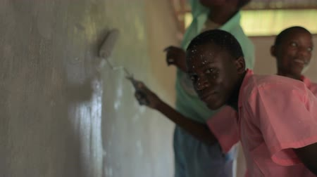 decorador : Children painting a wall in a village in Kenya two hours north of Africa city Mombassa Stock Footage
