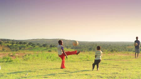 sul : Shot of children playing soccer on the fields in Kenya, Africa.