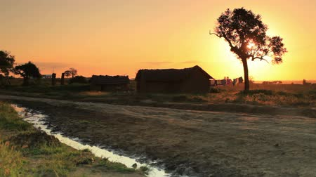 hladový : Shot of a dirt road and homes at sunset in Kenya, Africa. Dostupné videozáznamy