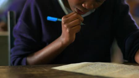 concentrando : Close up front view of student doing classwork in Kenya, Africa. Vídeos
