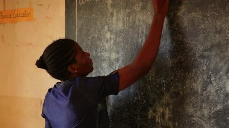 schooler : Close up of teacher and chalkboard in Kenya, Africa. Front view. Stock Footage